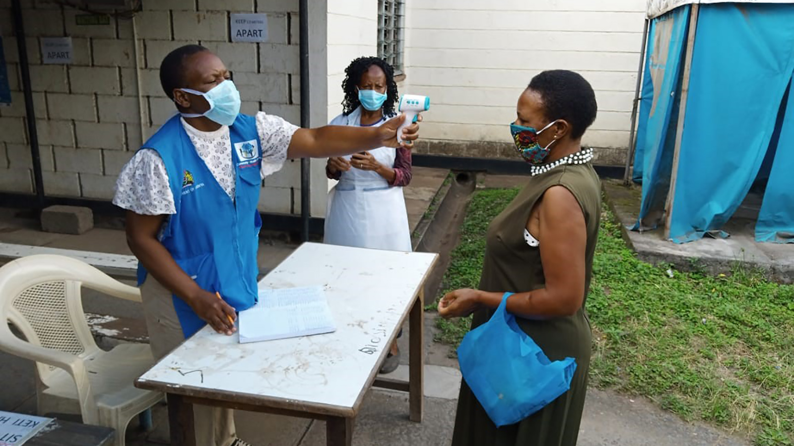 Community health volunteer taking temperatures at health facility in Nairobi.